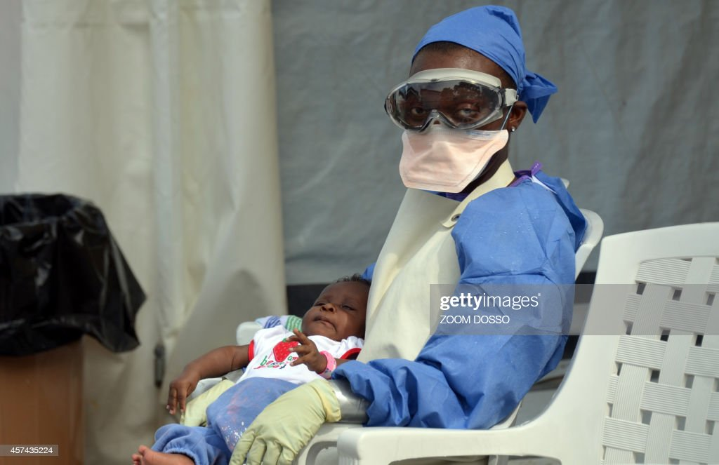 A Liberian health worker holds a baby infected with the Ebola virus on October 18 2014 at the NGO Medecins Sans Frontieres Ebola treatment center in...