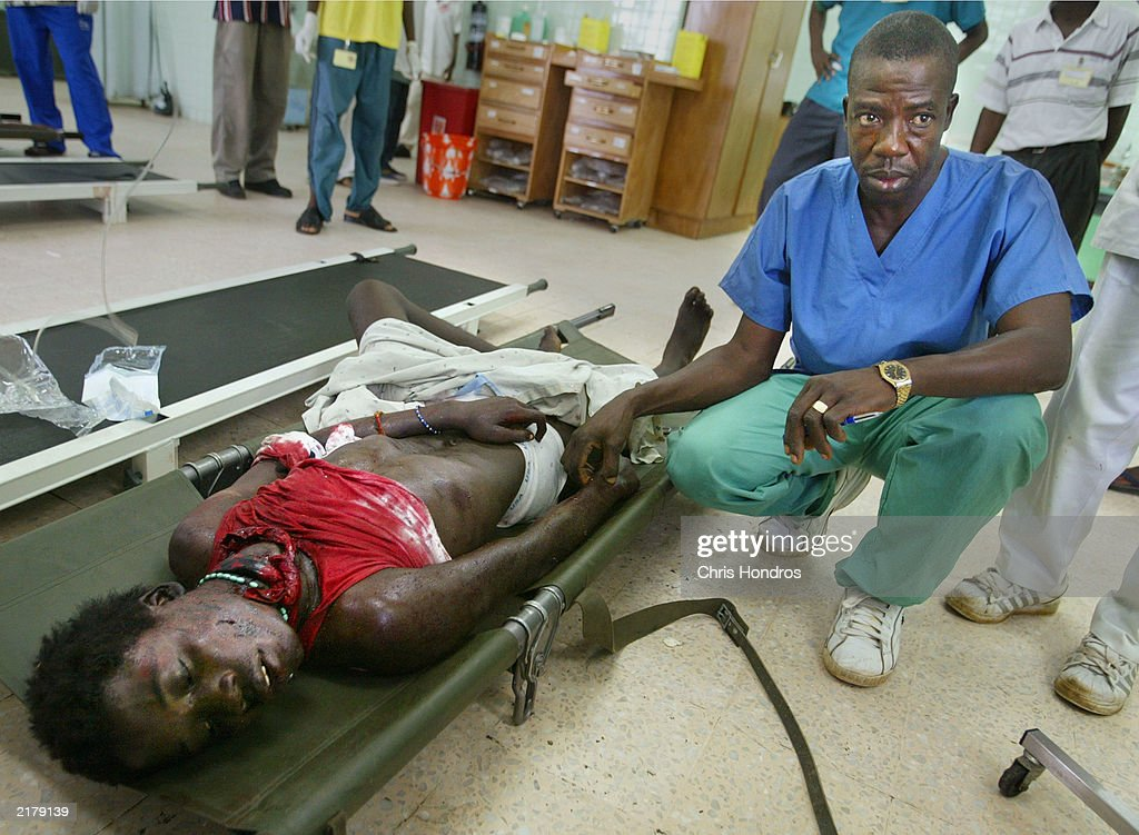 A Liberian medical assistant takes the pulse of a government soldier who was injured in fighting at JFK Hospital July 20, 2003 in Monrovia, Liberia. Government forces succeeded in forcing back rebel forces in fierce fighting on the edge of Monrovia's city center.