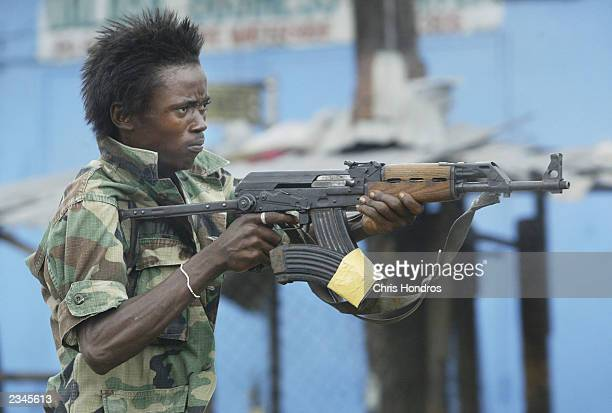 Liberian militia soldier loyal to the government fires on rebel forces across a key bridge on July 30 2003 in Monrovia Liberia Sporadic clashes...