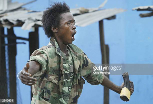 Liberian militia soldier loyal to the government taunts rebel forces across a key bridge on July 30 2003 in Monrovia Liberia Sporadic clashes...