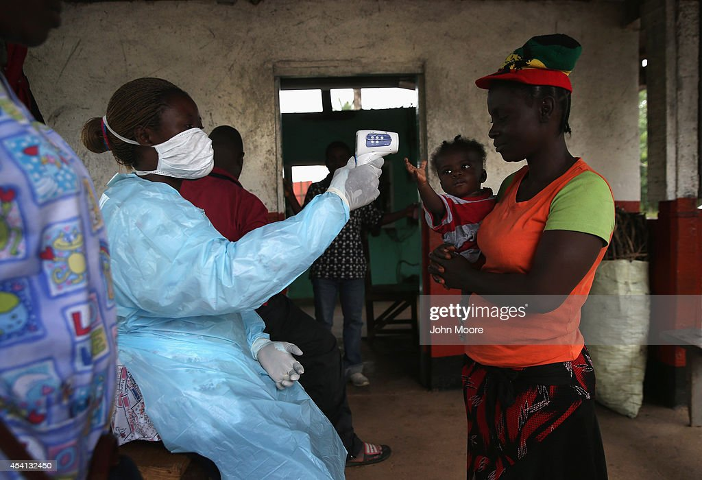 Liberian Ministry of Health worker checks people for Ebola symptoms at a checkpoint near the international airport on August 24 2014 near Dolo Town...
