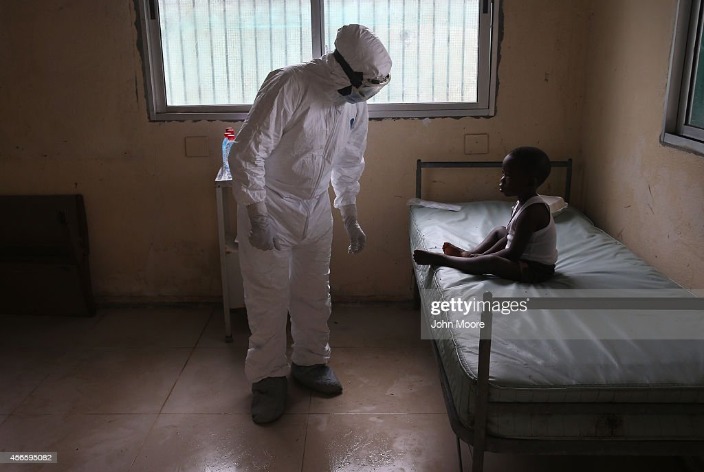 Liberian Ministry of Health worker dressed in an anticontamination suit speaks to Banu in a holding center for suspected Ebola patients at Redemption...