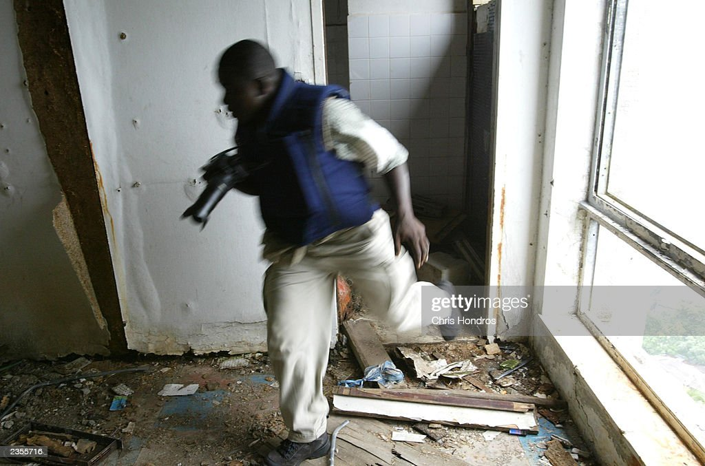 A Liberian news photographer runs for cover as bullets shatter a nearby window August 1, 2003 in Monrovia, Liberia. Many journalists have evacuated Liberia, where daily shellings and stray bullets make for dangerous work.