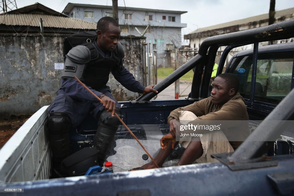 A Liberian policeman detains an accused looter on the second day of the government's Ebola quarantine on the West Point neighborhood on August 21, 2014 in Monrovia, Liberia. The government delivered bags of rice, beans and cooking oil to residents, who are forbidden from leaving the seaside slum, due to the Ebola outbreak in their community. More than 1,200 people have died due to the Ebola epidemic in West Africa.