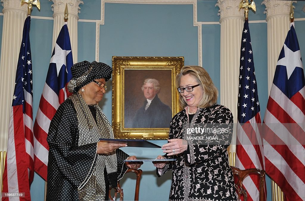 Liberian President Ellen Sirleaf Johnson (L) and US Secretary of State Hillary Clinton exchange documents after signing a strategic partnership agreement on January 15, 2013 at the State Department in Washington, DC. AFP PHOTO/Mandel NGAN