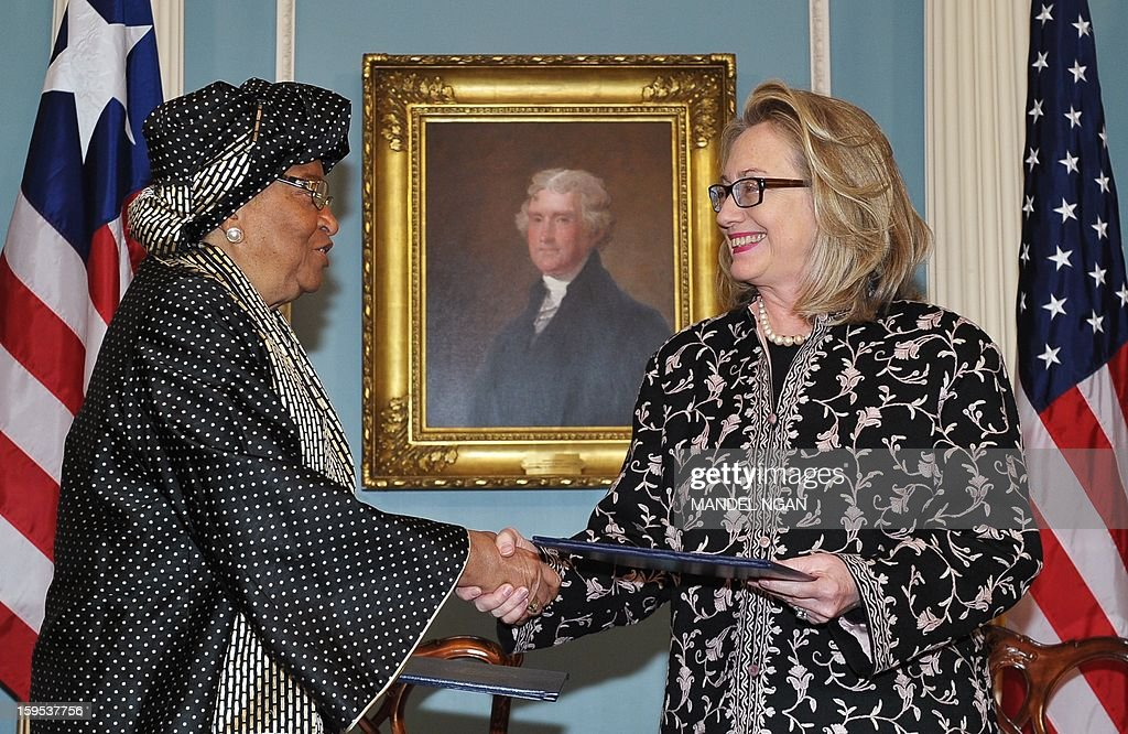 Liberian President Ellen Sirleaf Johnson (L) and US Secretary of State Hillary Clinton shakes hands as they exchange documents after signing a strategic partnership agreement on January 15, 2013 at the State Department in Washington, DC. AFP PHOTO/Mandel NGAN
