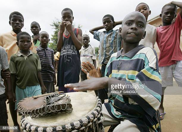 Liberian refugee children pose as one plays a drum on the United Nations World Refugee Day 20 June 2005 in the Buduburam Refugee Camp east of Accra...