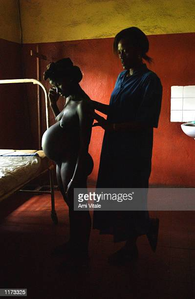 Liberian refugee Sata Fambullah 28yearsold is helped by a nurse as she begins experiencing labor pains before giving birth in a hospital July 16 2002...