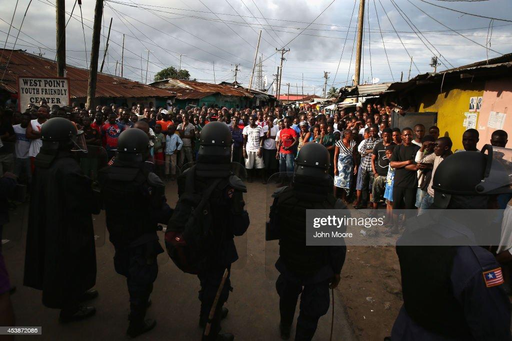 Liberian riot policemen enforce a quarantine on the West Point slum on August 20 2014 in Monrovia Liberia The quarantine of West Point a congested...