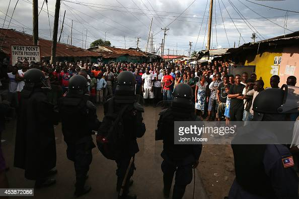 Liberian riot policemen enforce a quarantine on the West Point slum on August 20 2014 in Monrovia Liberia The quarantine of West Point a congested...