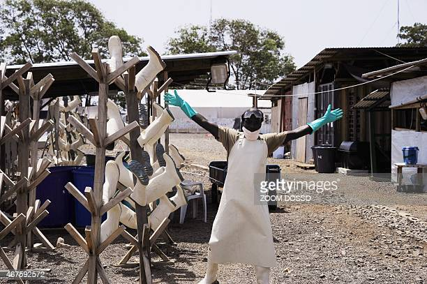 A Liberian worker reacts as he dismantles shelters in an Ebola treatment center closed by the charity Medecins Sans Frontiers in the Paynes Ville...