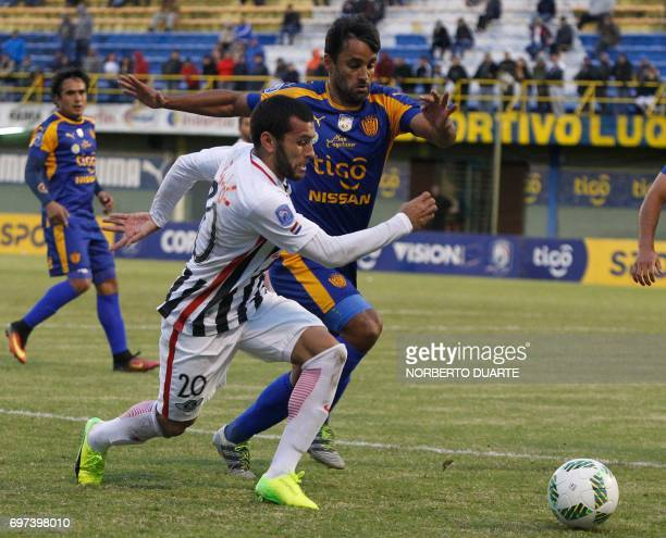 Libertad's footballer Antonio Bareiro vies for the ball with Juan Escobar of Sportivo Luqueno during their Paraguayan Apertura tournament match at...