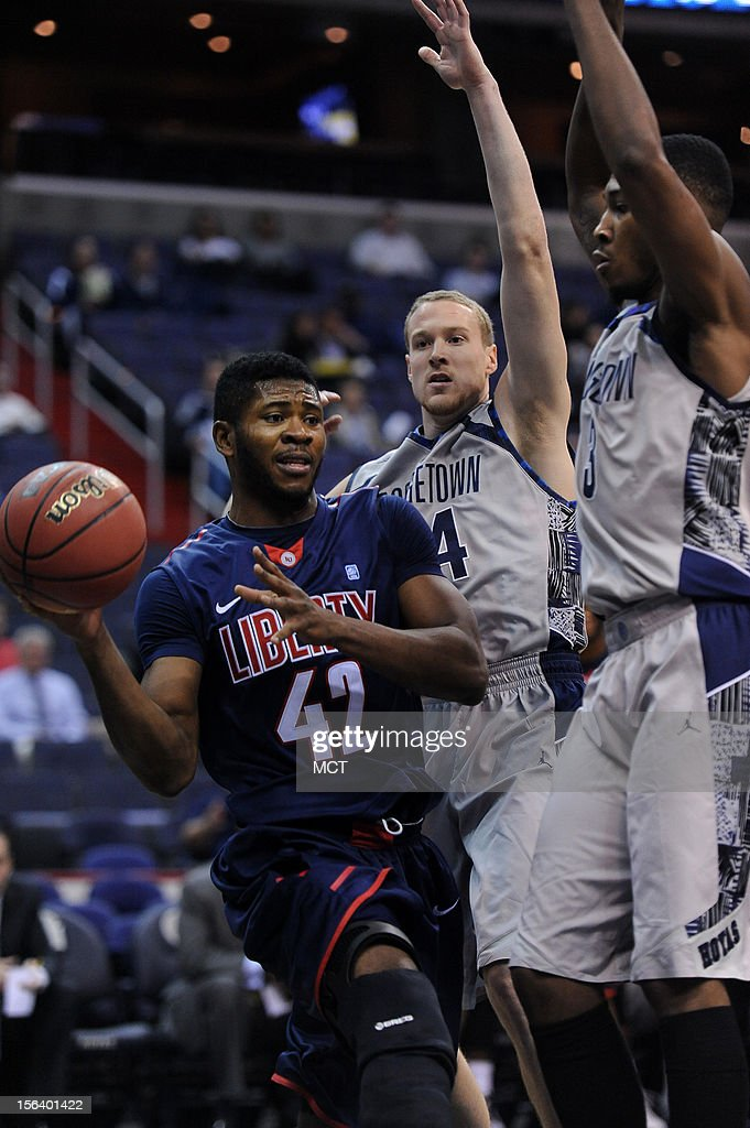 Liberty forward Sommy Ogukwe (42) dishes the ball as Georgetown forward Nate Lubick (34) and Georgetown forward Mikael Hopkins (3) apply pressure during the first half at the Verizon Center in Washington, D.C., Wednesday, November 14, 2012.