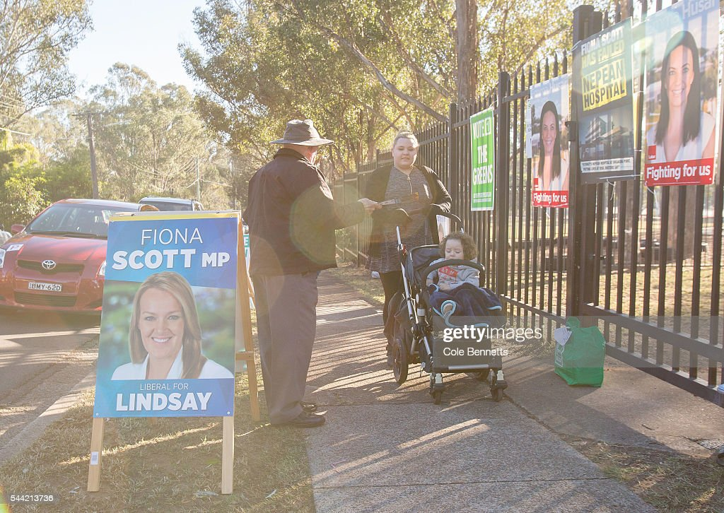 A Libral Party volunteer hands voting information to a woman as she goes to the polls at Kingswood Park Public School hall in the electorate of Lindsay on July 2, 2016 in Penrith, Australia. Voters head to the polls today to elect the 45th parliament of Australia.