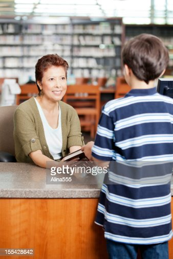 Librarian handing a book to little boy at checkout