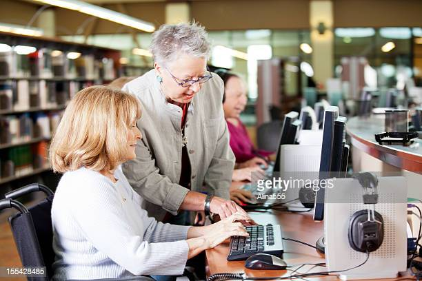 Librarian helping a group of seniors working on computers