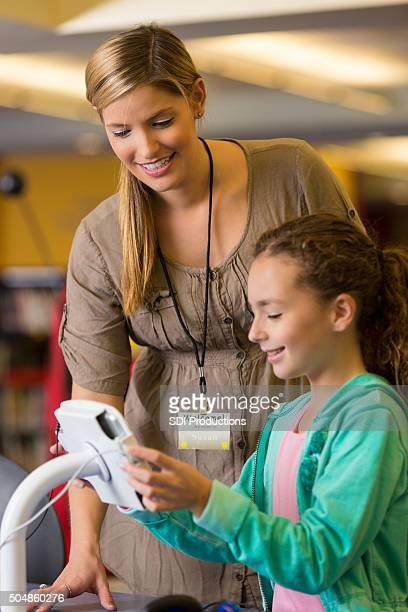 Bibliothekar helfen Kind im Grundschulalter Mädchen mit digitalen tablet in Bibliothek