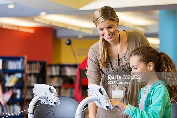 Librarian helping elementary age girl with digital tablet technology