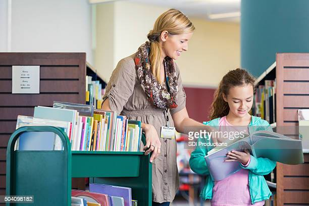Librarian helping elementary age student read book in library