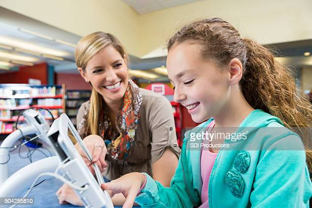 Librarian helping elementary student use digital tablet in library