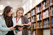 Librarian helping student with research in school library