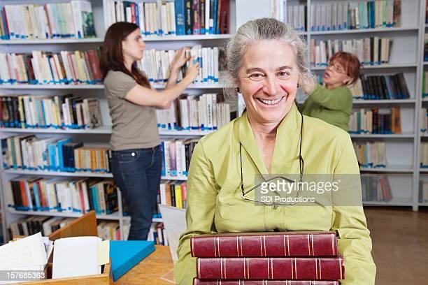 Bibliothécaire tenant une pile de livres de la bibliothèque