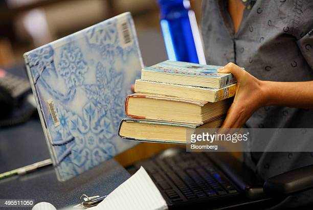 A librarian holds books at a checkout counter at the City of Santa Clarita Public Library Valencia branch in Santa Clarita California US on Sunday...
