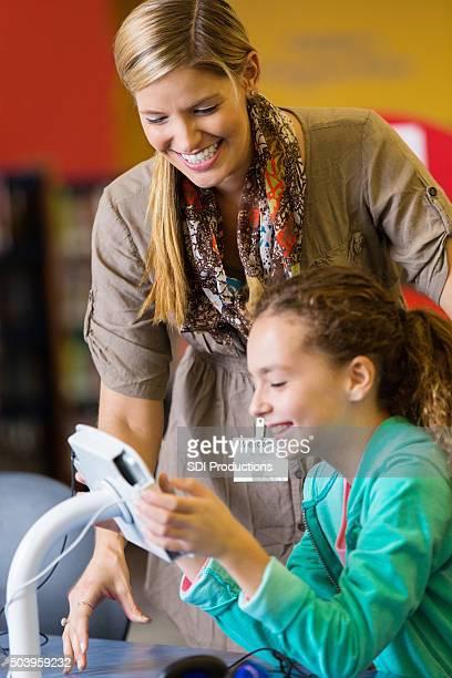 Bibliothécaire ou enseignant aidant Élève du primaire avec les nouvelles technologies