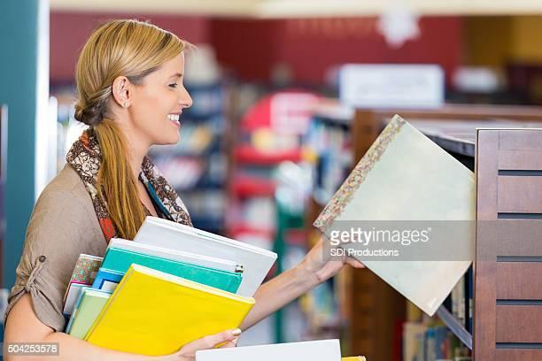 Bibliothécaire mettre des livres pour enfants de l'hôtel dans la section de la bibliothèque publique