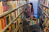 Librarian putting books back on shelves (wide angle)