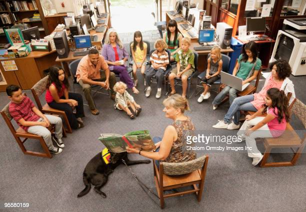 Librarian reading book to group of children