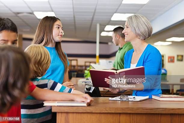 Librarian teacher helping students check out books in school library