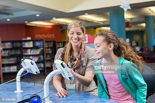Bibliotecario insegnamento piccola bambina di utilizzare talea digitale per Audiolibri