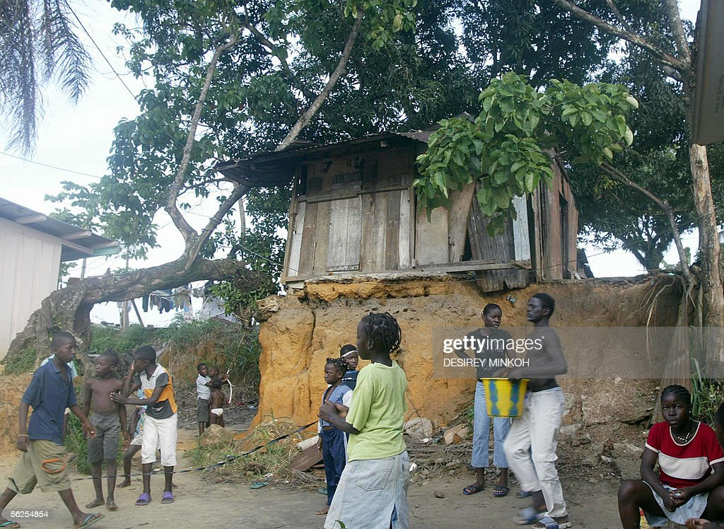 Youngsters play in front of a wooden makeshift hut with a corrugated roof housing a poor Gabonese family in La Baie des Cochons a poor estate of...