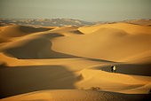 Libya, Fezzan, Sahara Desert, two people crossing Ubari Sand Sea