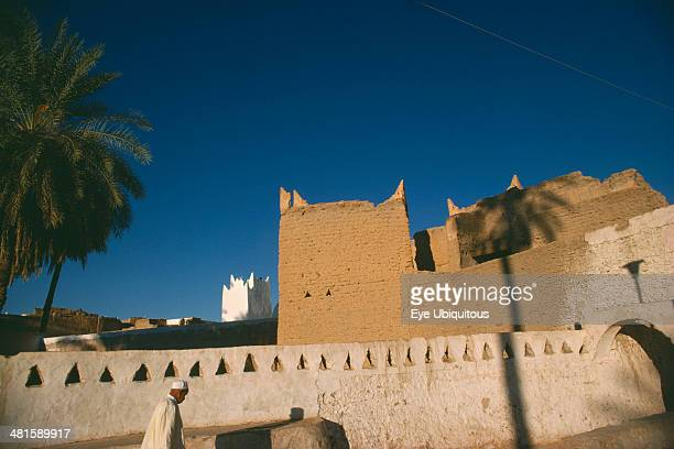 Libya Ghadames Oasis Man walking past whitewashed wall with mud brick town walls and white mosque minaret behind