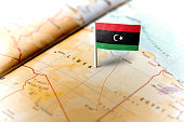 The flag of Libya pinned on the map. Horizontal orientation. Macro photography.