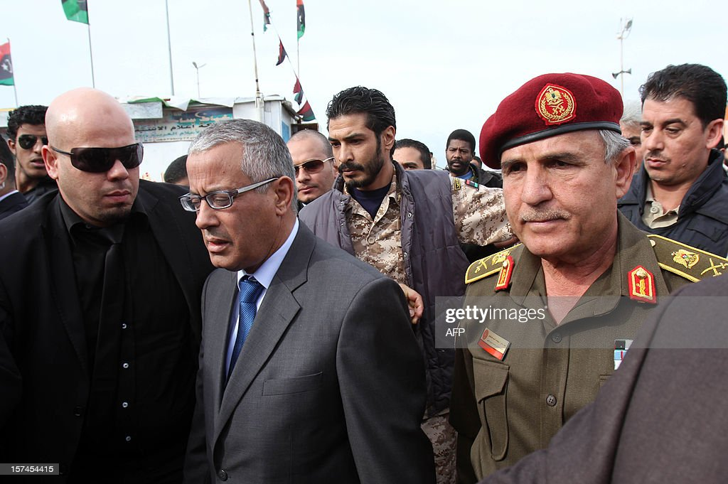 Libyan army Chief of Staff Yusef al-Mangush (R) and Ali Zaidan (2L), prime minister of Libya's interim government, attend the funeral procession of leading Libyan dissident Mansour al-Kikhia in the eastern Libyan port city of Benghazi on December 3, 2012. Kikhia, who disappeared 19 years ago under the Kadhafi regime, was buried weeks after his body was found in an intelligence services morgue, his brother said. AFP PHOTO / ABDULLAH DOMA