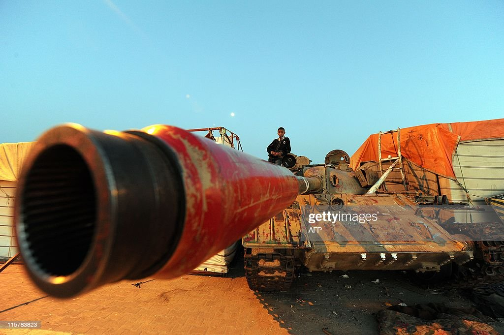 A Libyan boy sits on a tank parked in Benghazi's Revolution square on May 15, 2011. Kadhafi's prime minister offered on May 15 a truce to the visiting UN special envoy to Libya, Abdul-Ilah al-Khatib, in return for an immediate NATO ceasefire, as an anti-regime revolt entered a fourth month. AFP PHOTO/ Saeed KHAN