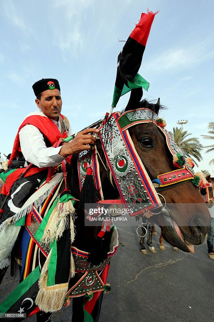 Libyan camel and Horse riders arrive in Tripoli's landmark Maryrs square to welcom the flame of Freedom and Development after it travelled from Benghazi, Sabah and Zuwahara marking the opening of the second Libyan International Fair on April 1, 2013 in Tripoli, Libya. Gunmen posing as security personnel kidnapped a top aide of Libyan Prime Minister Ali Zeidan, just hours after the premier revealed members of his government had received death threats, a cabinet source told AFP on Monday. AFP PHOTO/MAHMUD TURKIA