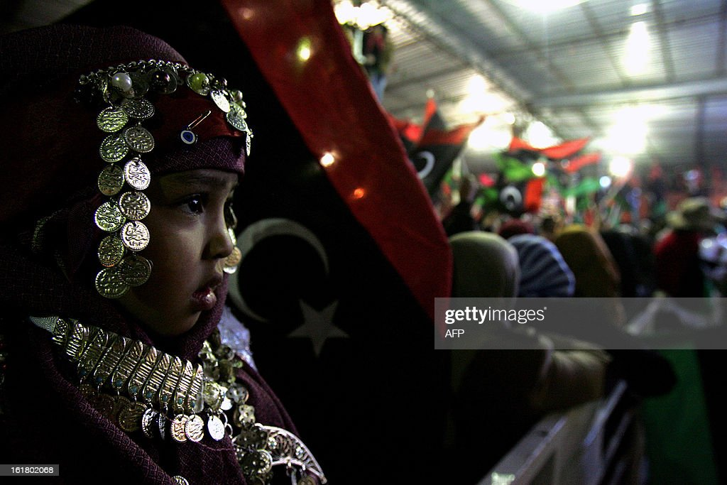 A Libyan child wearing traditional clothing looks on as hundreds of Libyans celebrate the upcoming second anniversary of the Libyan revolution, in Benghazi on February 16, 2013. Libya on Sunday will mark the second anniversary of the uprising that toppled the regime of strongman Moamer Kadhafi, amid fears of fresh violence and calls for demonstrations across the country. The government has already taken a series of measures to contain any attempt by supporters of the former regime to 'sow chaos' amid anger from protesters who accuse the new rulers of failing to push for reform.