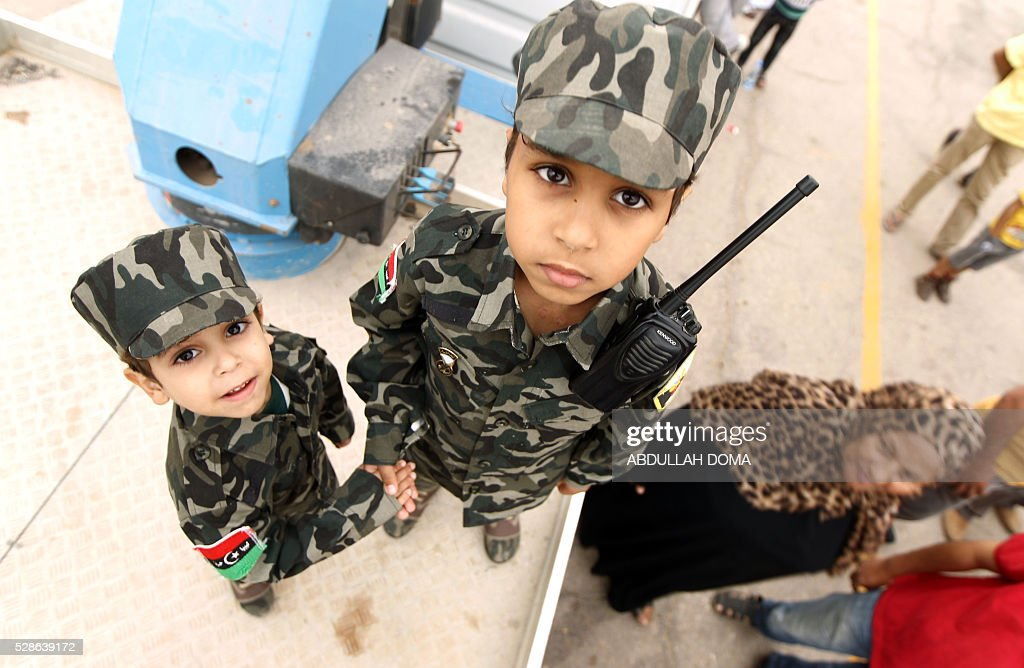 Libyan children dressed in military fatigues attend a demonstration in the eastern coastal city of Benghazi calling for military forces to re-capture the southern city of Sirte from the Islamic State (IS) group without foreign intervention on May 6, 2016. The head of Libya's unity government announced plans the previous month for a concerted campaign to drive the Islamic State group out of the North African country, but without foreign intervention. The unity government fears that separate operations in Sirte could spark clashes between the multitude of different fighting forces in Libya and play into the jihadists' hands. DOMA