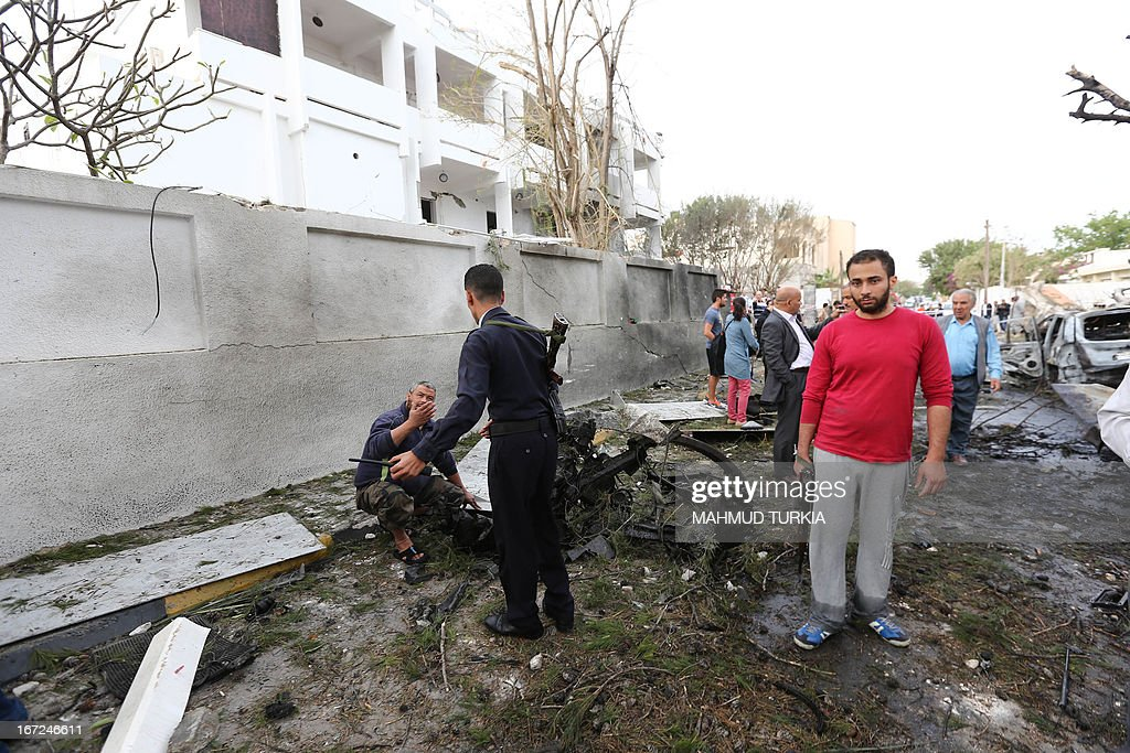 Libyan civilians and security forces gather near the destroyed wall of the French embassy in Tripoli following a car bomb, on April 23, 2013. A car bomb blasted the embassy of France in Tripoli, injuring two French guards and causing serious damage to the building, embassy and Libyan sources said.