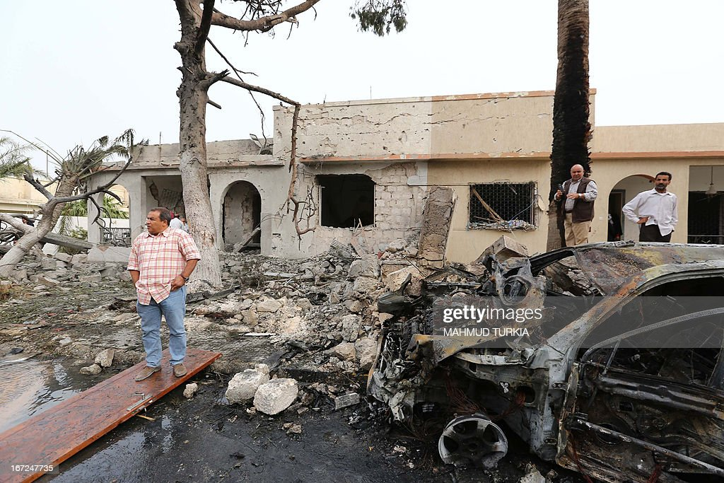 Libyan civilians gather across the street from the French embassy building (unseen) in Tripoli following a car bomb attack, on April 23, 2013. A car bomb blasted the embassy of France in Tripoli, injuring two French guards and causing serious damage to the building, embassy and Libyan sources said.