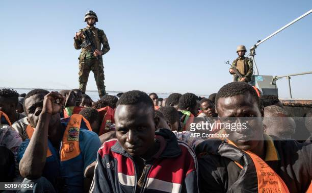 Libyan coast guardsmen stand on a boat during the rescue of 147 illegal immigrants attempting to reach Europe off the coastal town of Zawiyah 45...