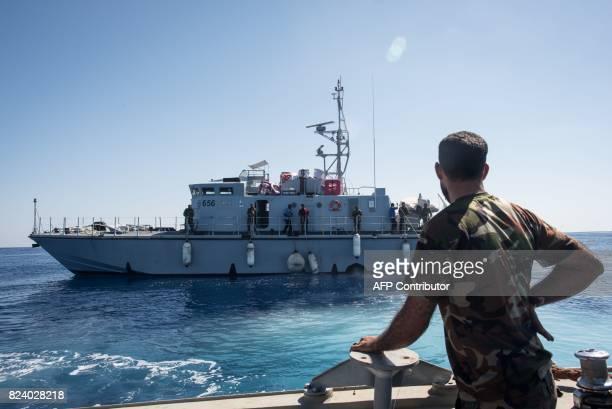 A Libyan coastguard looks towards a ship as he patrols the area at sea between Sabratha and Zawiyah on July 28 2017 / AFP PHOTO / TAHA JAWASHI