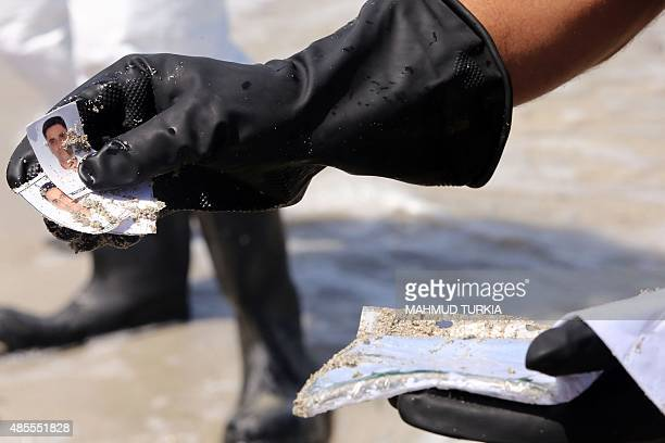 A Libyan coastguard shows pictures and documents found on the body of a migrant that had washed ashore on a beach on August 28 2015 in the port town...