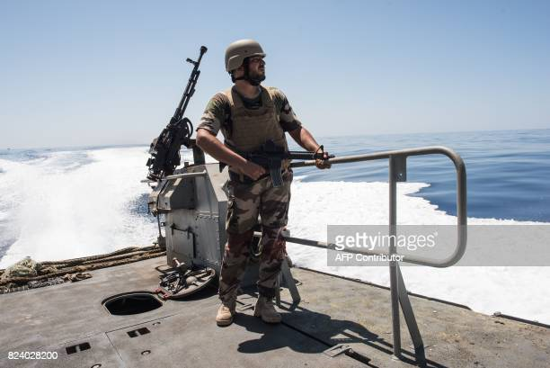 A Libyan coastguard stands next to a mounted gun on a boat as he patrols the area at sea between Sabratha and Zawiyah on July 28 2017 / AFP PHOTO /...