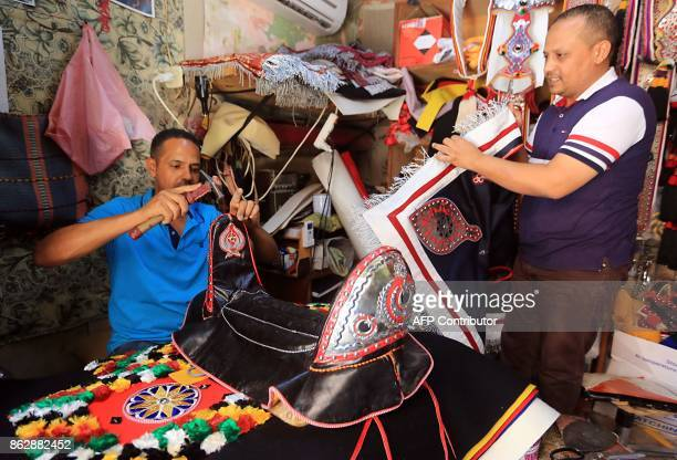A Libyan craftsman displays a traditional saddle that is used in Fantasia horse shows in the Libyan capital Tripoli on July 20 2017 For the...