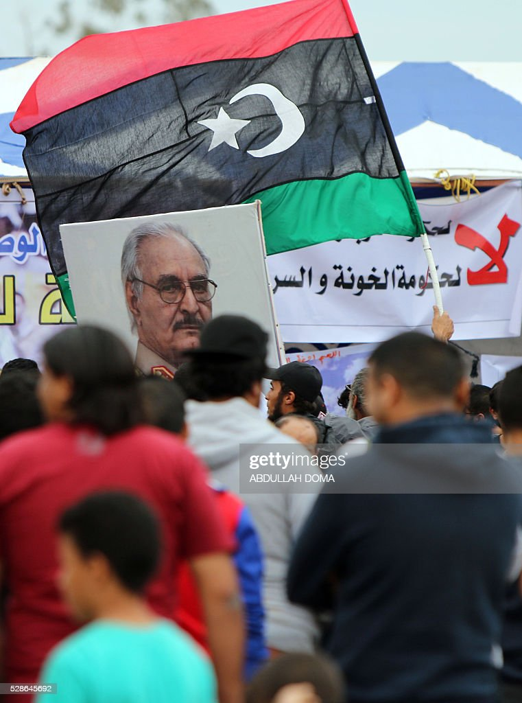 A Libyan demonstrator holds an image of General Khalifa Haftar (R), commander of the armed forces loyal to the internationally recognised Libyan government and the country's national flag during a protest in the eastern coastal city of Benghazi calling for military forces to re-capture the southern city of Sirte from the Islamic State (IS) group without foreign intervention on May 6, 2016. The head of Libya's unity government announced plans the previous month for a concerted campaign to drive the Islamic State group out of the North African country, but without foreign intervention. The unity government fears that separate operations in Sirte could spark clashes between the multitude of different fighting forces in Libya and play into the jihadists' hands. / AFP / ABDULLAH